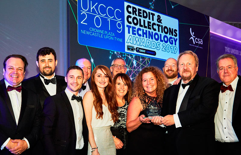 CCICM Director Carl Hackman (centre right) and Consumer Collections manager Heulwen Jones (centre left) hold the CSA CAI Award, watched by many of CCICM's senior managers and collectors, and joined by CSA President John Ricketts (far right) and TV actor Shaun Williamson (far left). Credit: Hannah Taylor, The Lens Box.